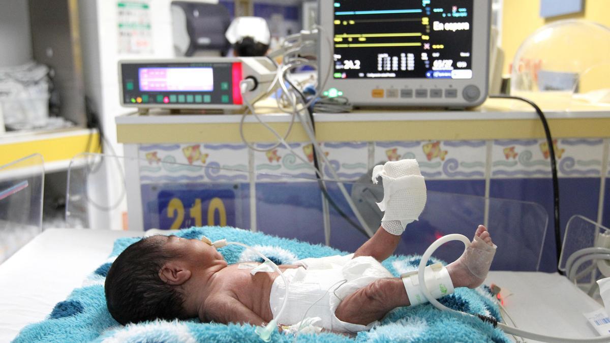 Un bebé prematuro en una incubadora. Foto de archivo