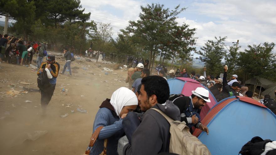 Los agentes macedonios lanzan granadas para aturdir a los inmigrantes que esperan para cruzar la frontera cerca de la estación de tren de Indomeni, al norte de Grecia. / Darko Vojinovic - AP