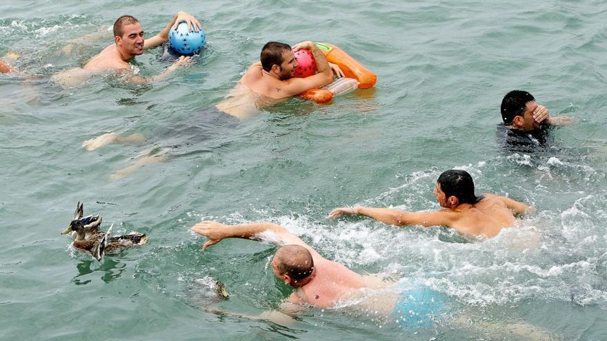 Dos nadadadores pugnan por coger un pato en las cucañas marítimas del Puerto de Sagunto