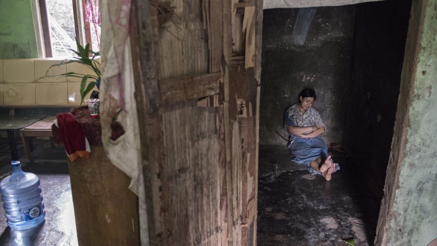Ernawati solo ve la luz cuando su madre la limpia o le da de comer, muchas veces un vaso de plástico con pipas o frutos secos.