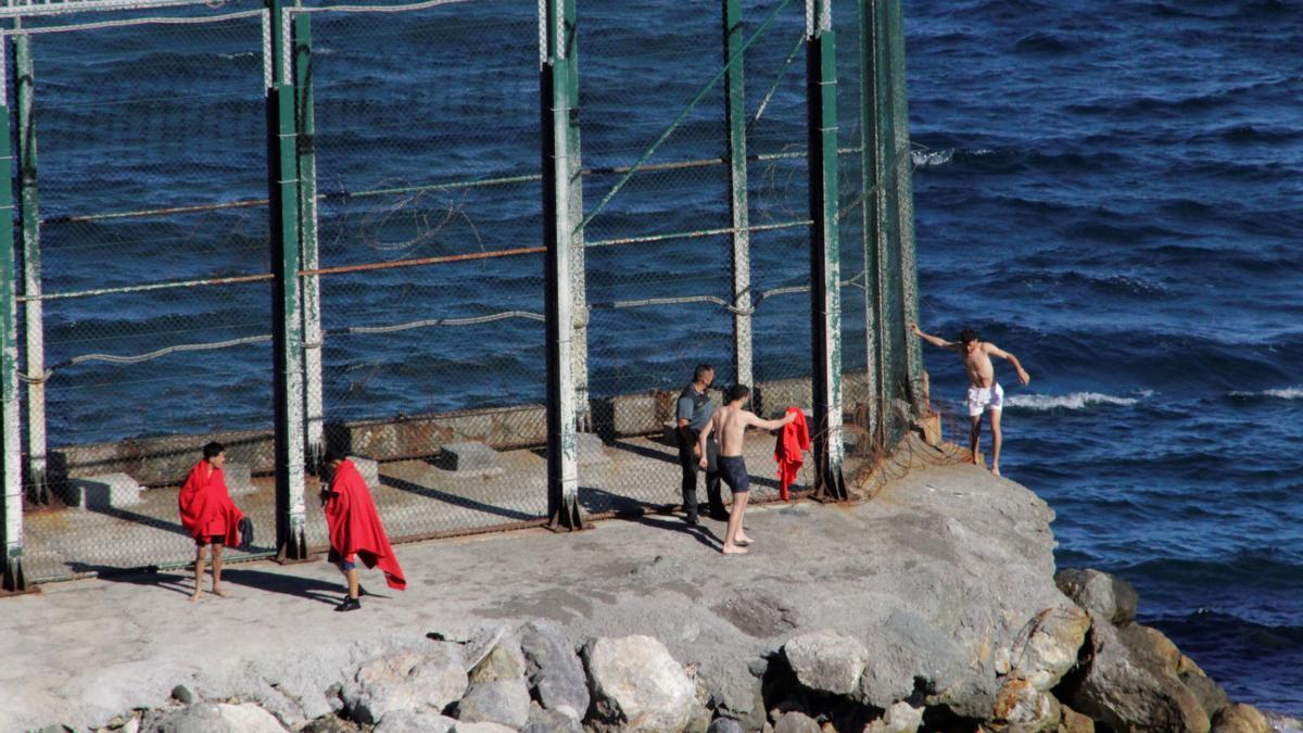 Un grupo de siete inmigrantes marroquíes, entre ellos tres menores, han llegado esta mañana aCeutapor el espigón sur del Tarajal, y uno de ellos ha tenido que ser rescatado por la Guardia Civil ante la dificultad para llegar a nado a la costa ceutí. EFE/ Reduan Dris