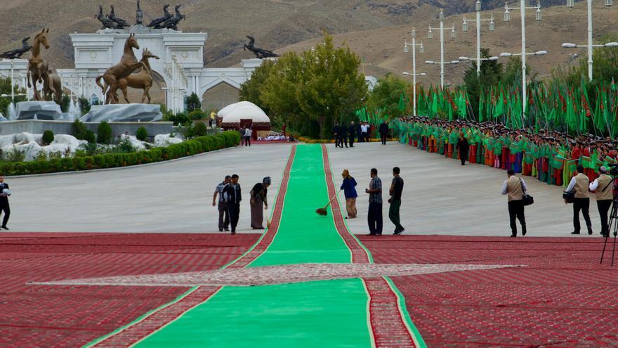 Las limpiadoras repasan la kilométrica alfombra por la que entrará Berdimuhamedov.