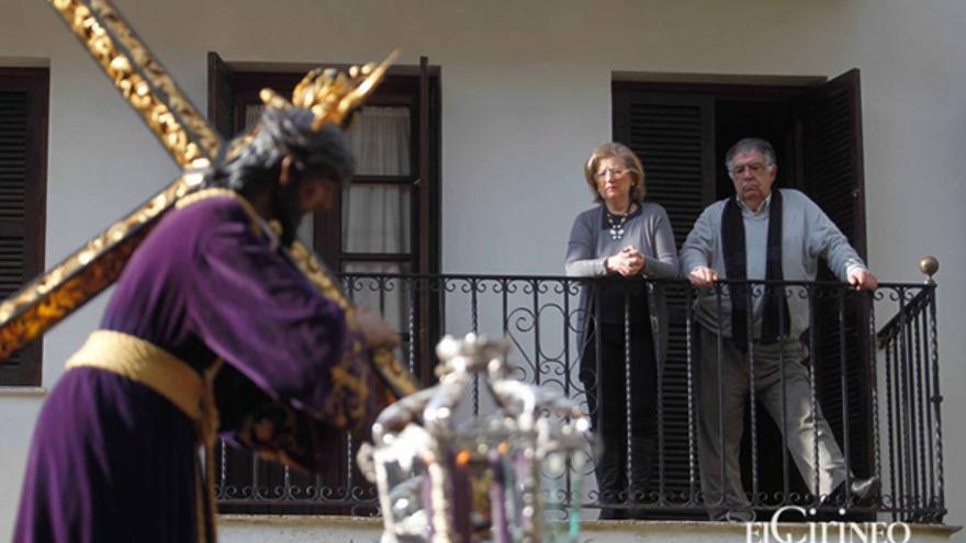 Personas contemplando el paso de una procesión desde un balcón | MADERO CUBERO