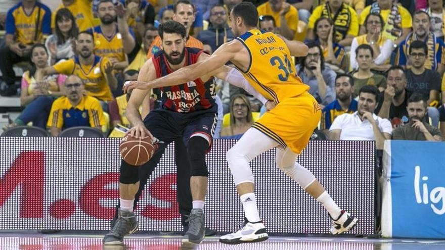 El escolta georgiano del Baskonia, Tornike Shengelia (i), intenta superar la defensa del jugador de Herbalife Gran Canaria, Pablo Aguilar, en el Gran Canaria Arena. EFE / Quique Curbelo.