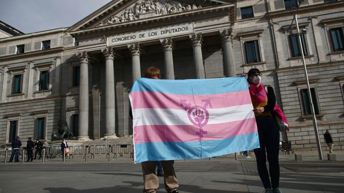 Dos personas sostienen una bandera trans durante una concentración convocada frente al Congreso de los Diputados en Madrid (España), a 18 de febrero de 2021