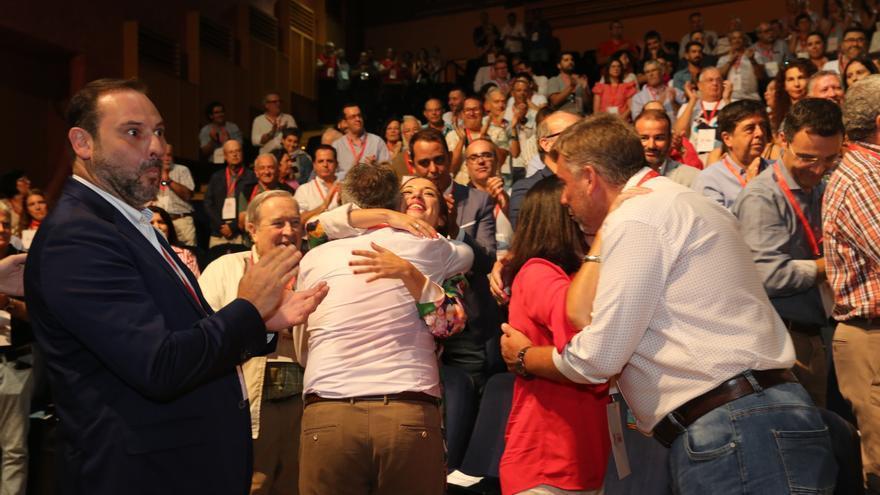 Ángel Víctor Torres y Patricia Hernández se abrazan. A la izquierda de la imagen, José Luis Ábalos.