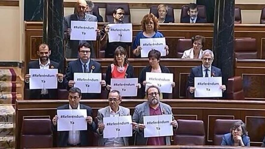 Los parlamentarios de la Izquierda Plural muestran carteles en favor de un referéndum en el hemiciclo