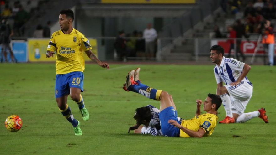 Jonathan Viera controla el balón con Vicente Gómez en el suelo.