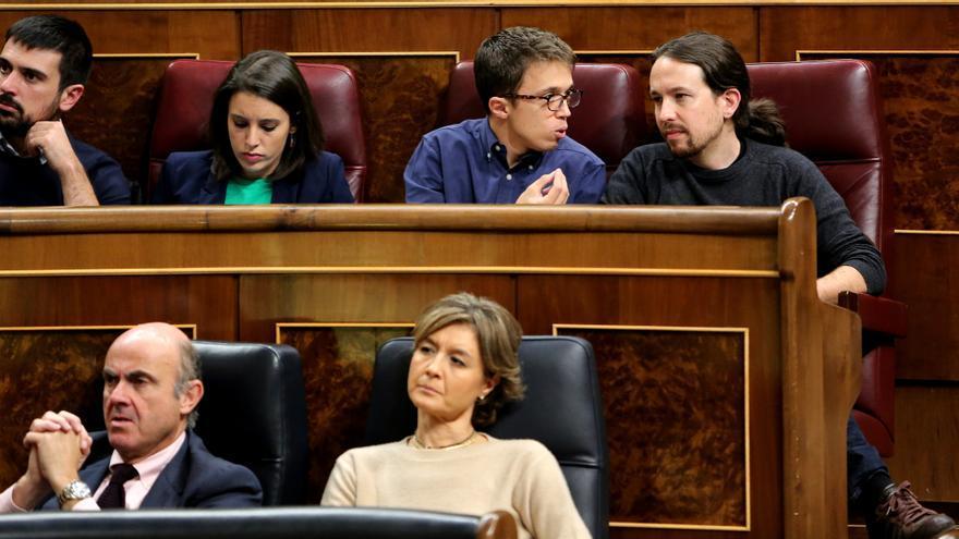 Pablo Iglesias, Íñigo Errejón e Irene Montero, diputados de Podemos, desde sus escaños este miércoles 26 de octubre. En la fila inferior, Isabel García Tejerina y Luis de Guindos