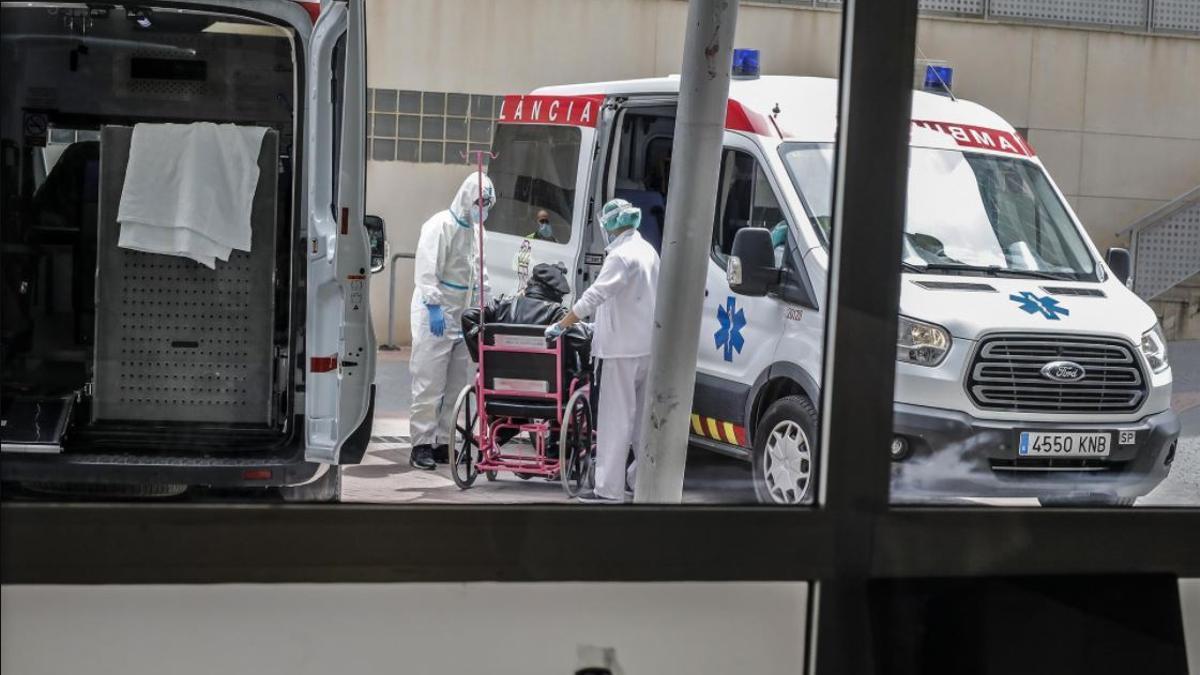 Personal sanitario protegido totalmente recibe a un paciente con coronavirus para ser atendido en el Hospital Arnau de Vilanova (València).