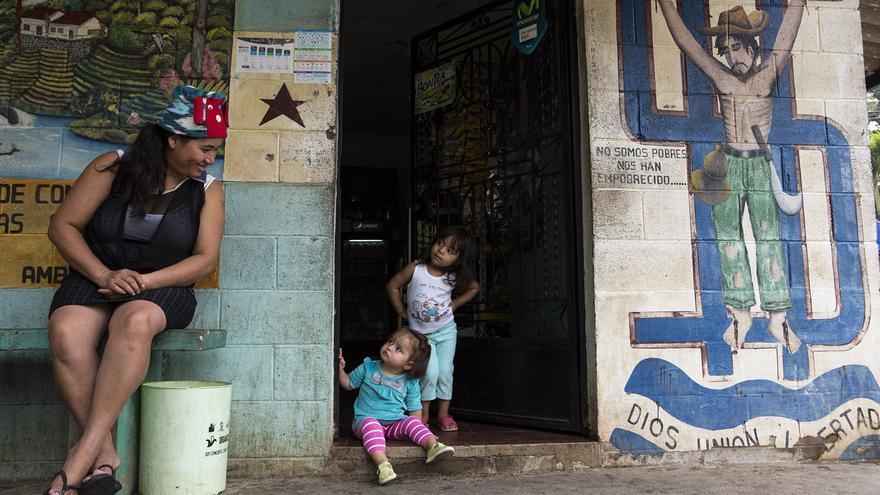 En el centro de Nueva Trinidad, una madre juega con sus hijas frente a un mural donde aparece un migrante crucificado sobre un símbolo del dólar