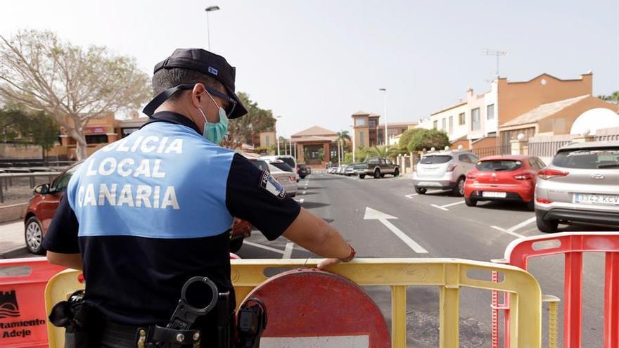 Un agente de policía coloca una valla para prohibir el paso al hotel situado en el municipio tinerfeño de Adeje. EFE/Ramón de la Rocha