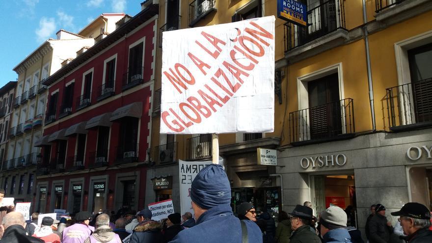 """Un hombre sostiene una pancarta con el mensaje """"No a la globalización"""" en la manifestación de pensionistas, taxistas y afectados por la hipoteca en Madrid."""