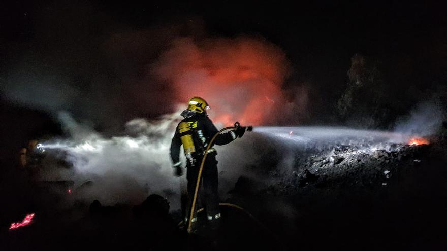 En la imagen, dos bomberos durante las tareas de extinción del incendio registrado la pasada madrugada en el antiguo vertedero de El Paso.