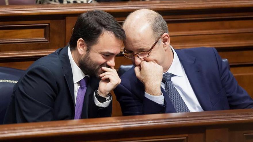 Los consejeros de Presidencia y de Economía del Gobierno de Canarias, Aarón Afonso (i) y Pedro Ortega, respectivamente, en un momento del pleno del Parlamento de Canarias.