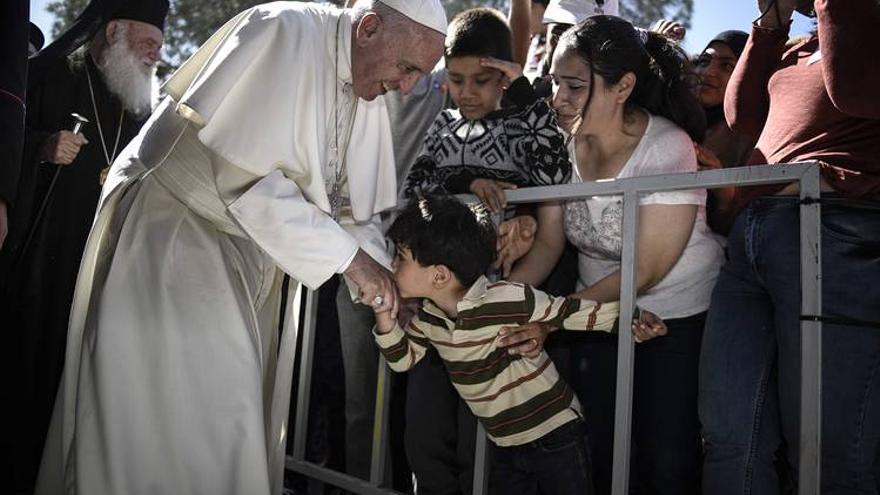 Un niño besa la mano del Papa durante la visita al campo de detención de refugiados de Moria, en Lesbos (Grecia)