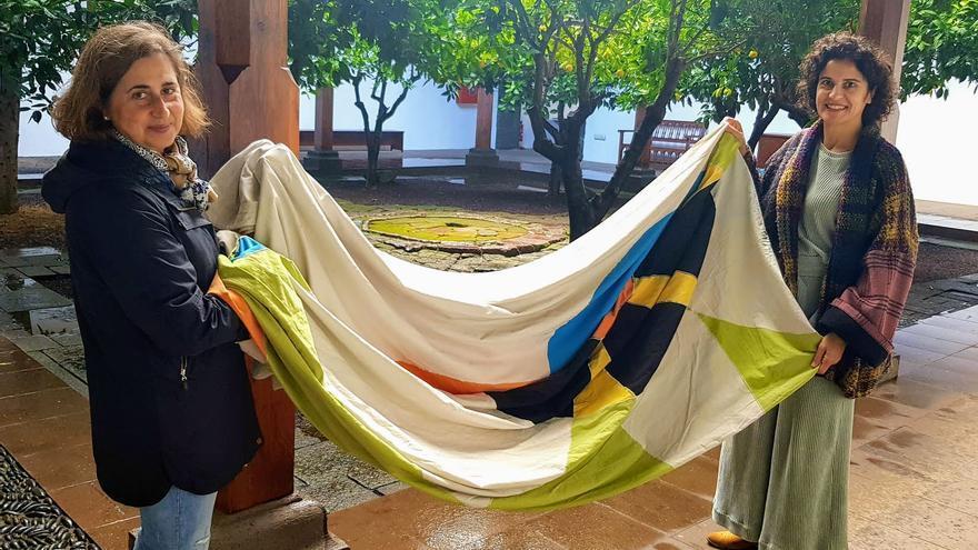 Isa Santos (i),  técnica del Centro de Restauración del Cabildo  de La Palma, y Jovita Monterrey,  consejera insular de Cultura y Patrimonio Histórico, con una de las banderas del Cosmos diseñada por César Manrique.