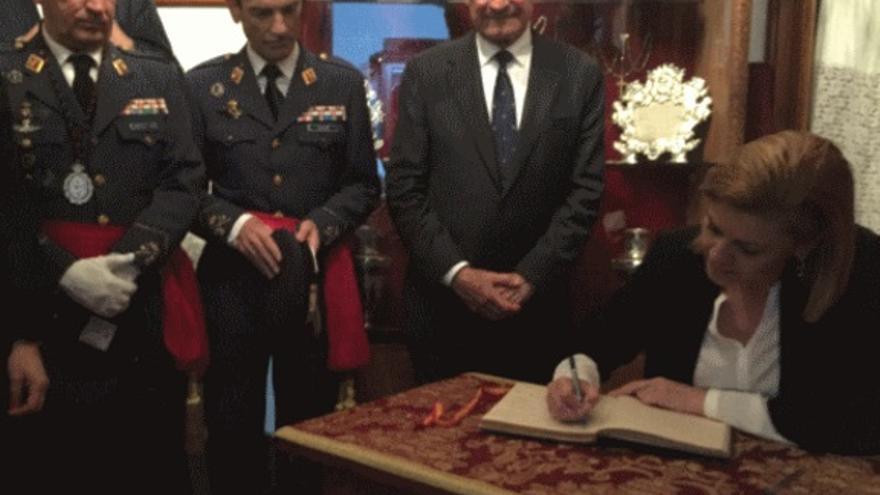Cospedal firma en el libro de la Hermandad de La Misericordia en presencia del alcalde y de militares