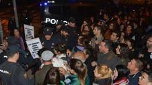 Manifestantes de la concentración feminista intentan atravesar las vías del tren, bloqueadas por la Policía Nacional.