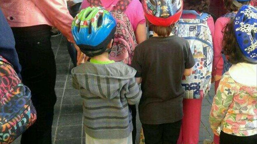 Niños acudiendo al Colegio Cervantes con casco. Foto vía @vicentjuanmtnez