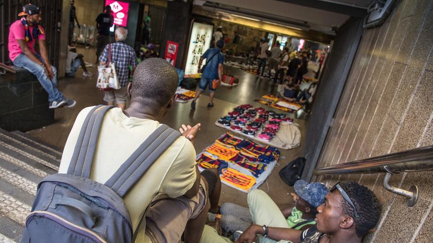 Varios vendedores ambulantes en la entrada del metro de Plaça Catalunya / SANDRA LÁZARO
