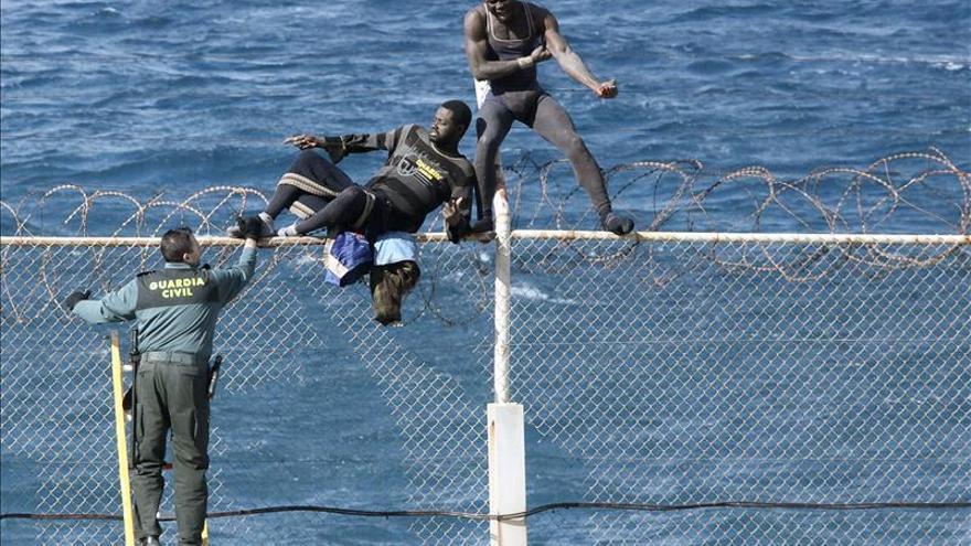 Varios inmigrantes permanecen encaramados a una valla fronteriza de Ceuta. / EFE.