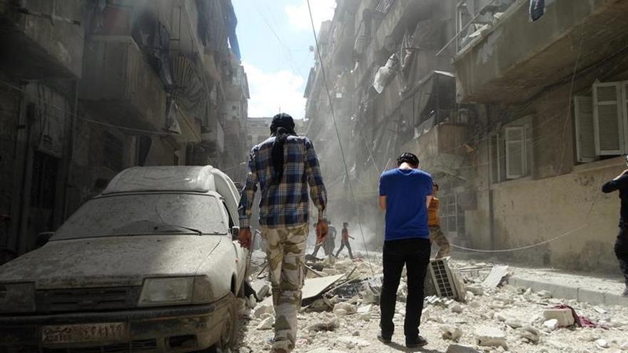 Un par transeúntes recorre algunas de las calles de Alepo (Siria) que sufrieron ataques aéreos este 28 de abril.