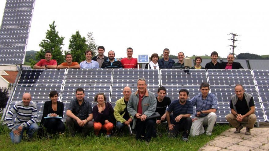 Miembros de la cooperativa posan junto a placas de energía fotovoltaica.