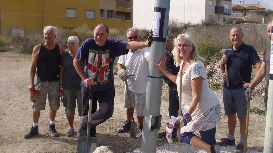 El británico Allan Sharpe, con una pala en la mano, recogiendo basura junto con otros voluntarios en el municipio murciano de Fortuna