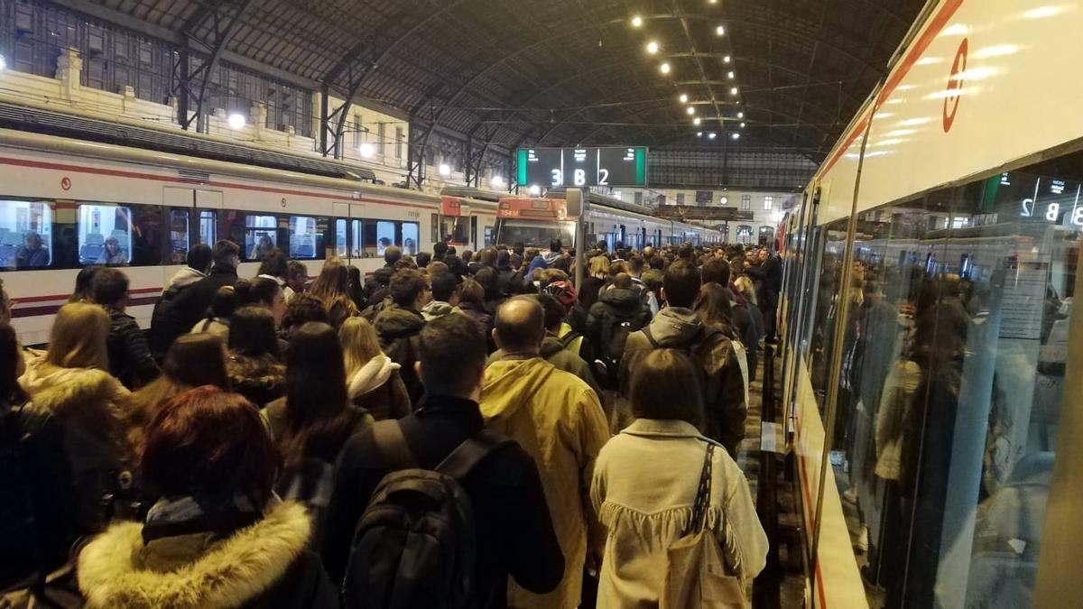 Nombrosos usuaris esperen l'arribada, amb retard, d'un tren de Rodalia en l'estació del Nord de València.
