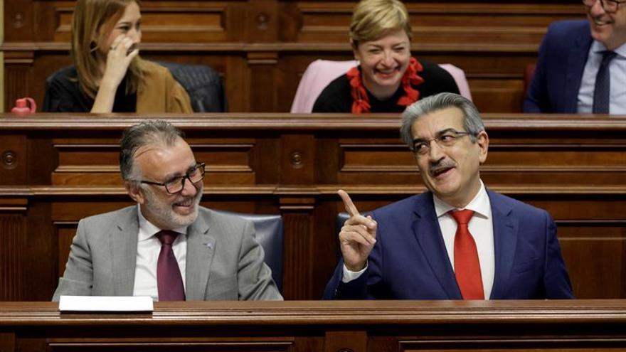 El consejero de Hacienda del Gobierno de Canarias, Román Rodríguez (d), bromea con el presidente, Ángel Víctor Torres (i).