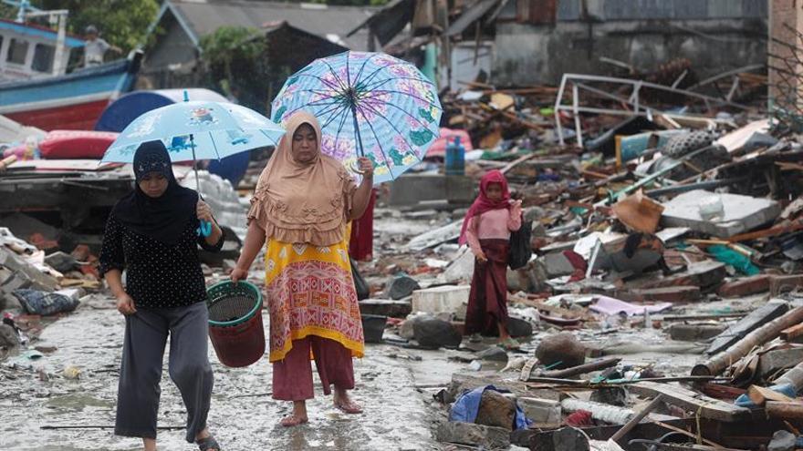 Los ciudadanos caminan bajo la lluvia entre los escombros tras el tsunami que golpeó el Estrecho de Sonda en Sumur, Indonesia.