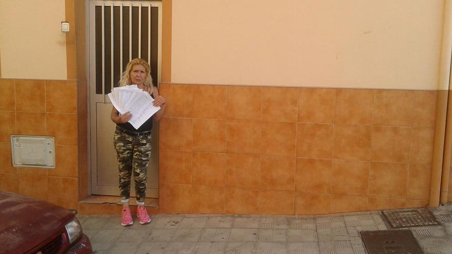 Luisa Hernández posa junto a las firmas recogidas entres sus vecinos