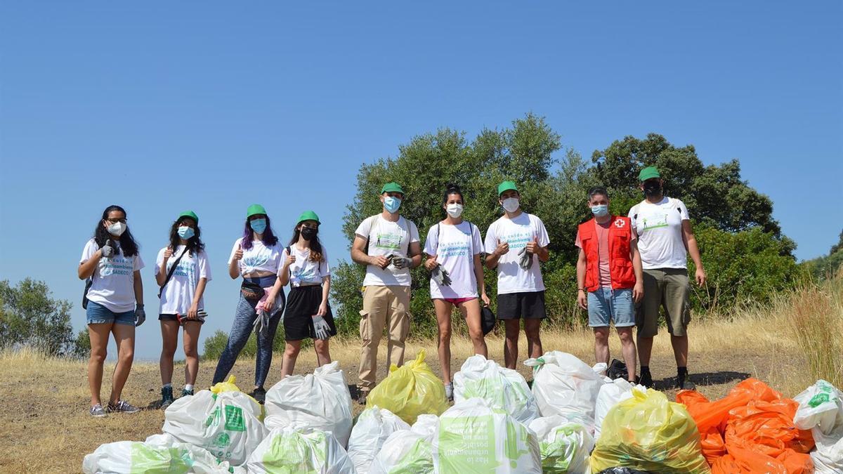 Voluntarios de Cruz Roja recogen basura en la naturaleza.