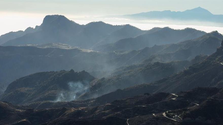 Zonas afectadas por el fuego del incendio forestal, vistas desde la cruz de Tejeda, con el Teide (Tenerife) al fondo.