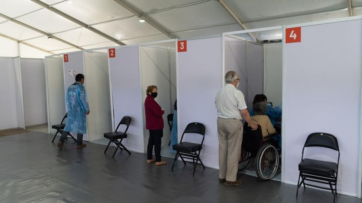 Personas mayores se preparan para recibir una dosis de la vacuna contra el coronavirus Sinovac en el primer día de vacunación masiva, en un centro de vacunación montado en el Estadio Bicentenario.