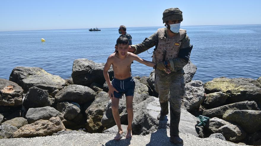 Un militar del ejército español ayuda a un menor migrante procedente de Marruecos a su llegada a Ceuta, a 19 de mayo de 2021, en Ceuta, (España). Los intentos de llegar a Ceuta no han cesado desde el lunes y pasadas 72 horas el balance de migrantes que ha