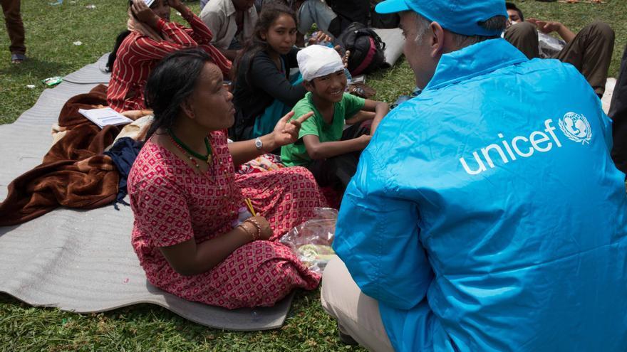 Un voluntario de Unicef atiende a una refugiada nepalí