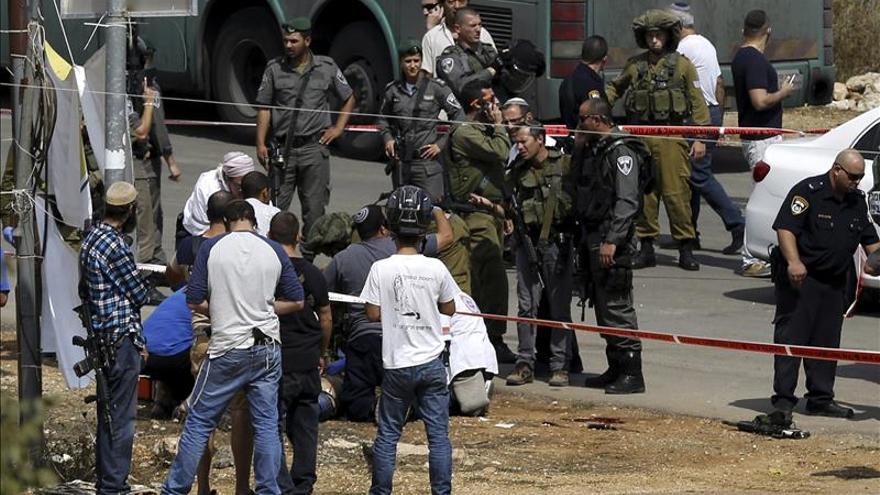 Colonos israelíes y soldados rodean a un palestino herido tras un ataque contra un policía en el asentamiento de Kiryat Arbá, en la localidad palestina de Hebrón hoy. / EFE.