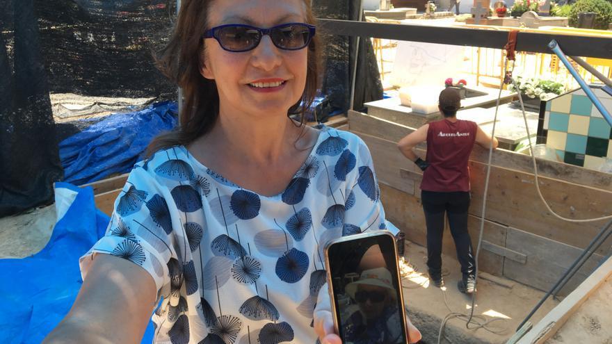 Arlette Pujol sostiene una una foto de su madre en el móvil ante la fosa de Paterna