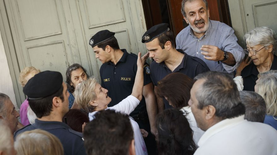 Descripción: Pensioners try to get a number to enter inside a bank in Athens, Wednesday, July 1, 2015. About 1,000 bank branches around the country were ordered by the government to reopen Wednesday to help desperate pensioners without ATM cards cash up to 120 euros ($134) from their retirement checks. Eurozone finance ministers were set to weigh Greece's latest proposal for aid Wednesday. / AP Photo
