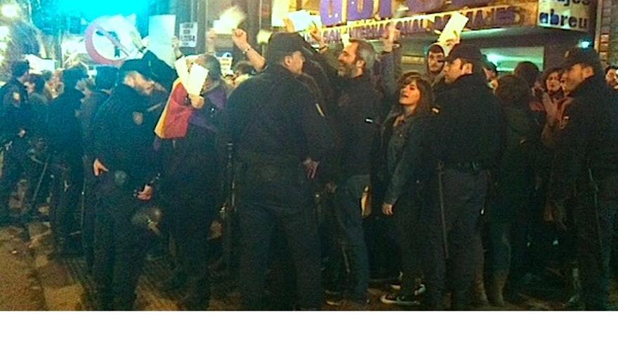 Personas alzando sobres frente a la sede del PP de Madrid