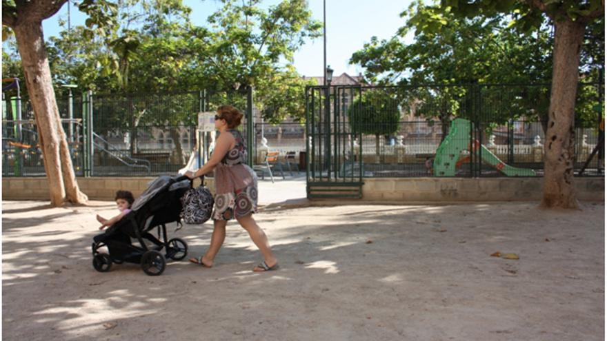 Una mujer pasea a su bebé por un parque