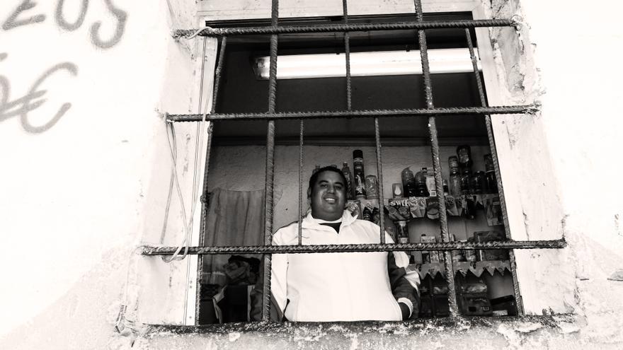 Faisal Benani tras la reja de su pequeña tienda de alimentación