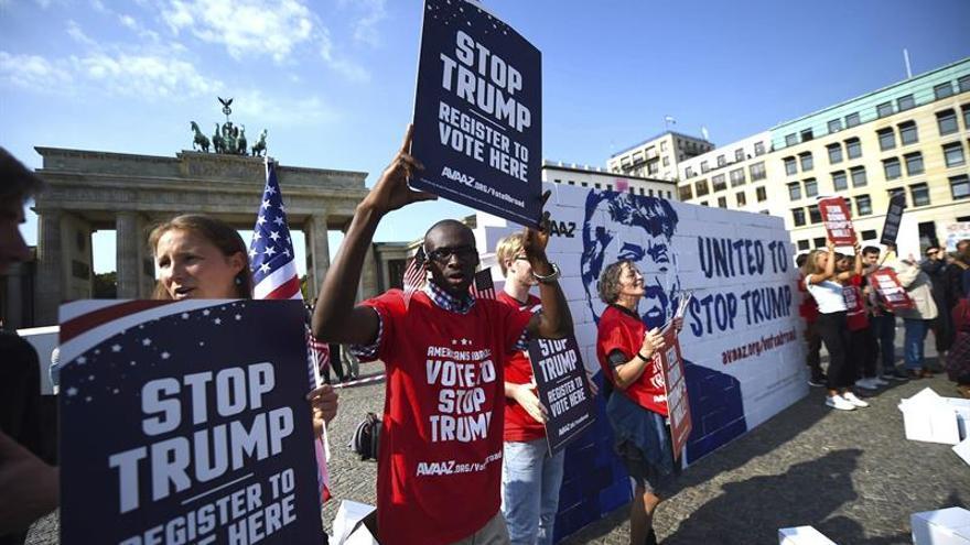 Unos activistas levantan y derriban el muro de Trump ante la Puerta de Brandeburgo