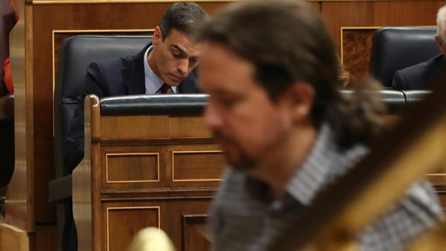 El líder de Unidas Podemos, Pablo Iglesias, pasa ante el presidente del Gobierno en funciones, Pedro Sánchez.