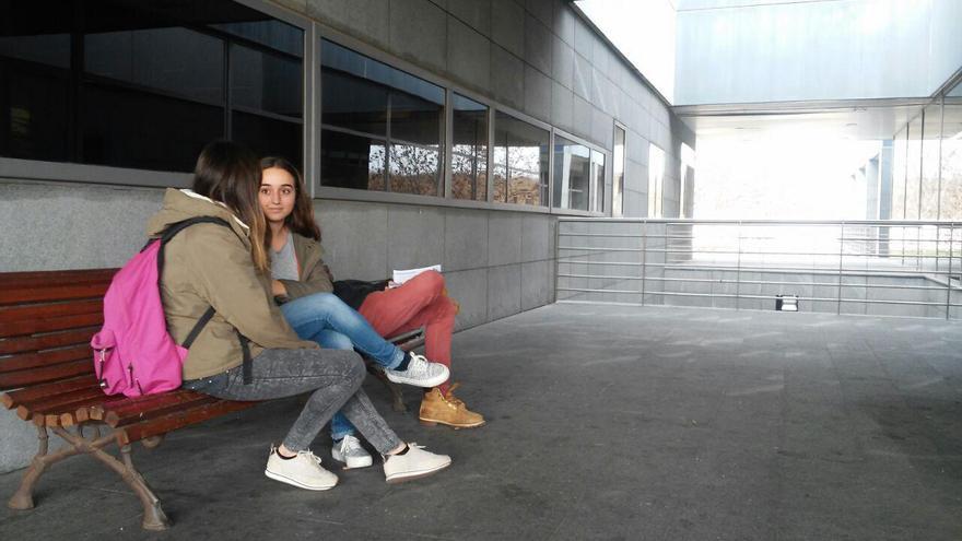 Varias estudiantes sentadas en un banco a la puerta de la biblioteca del campus de Móstoles.