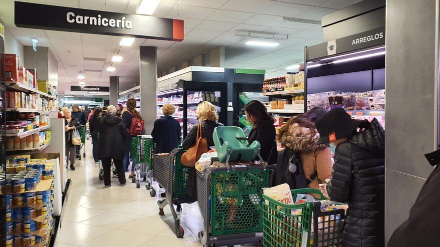 Decenas de personas cargadas de provisiones esperan para poder pagar en un supermercado en Madrid.