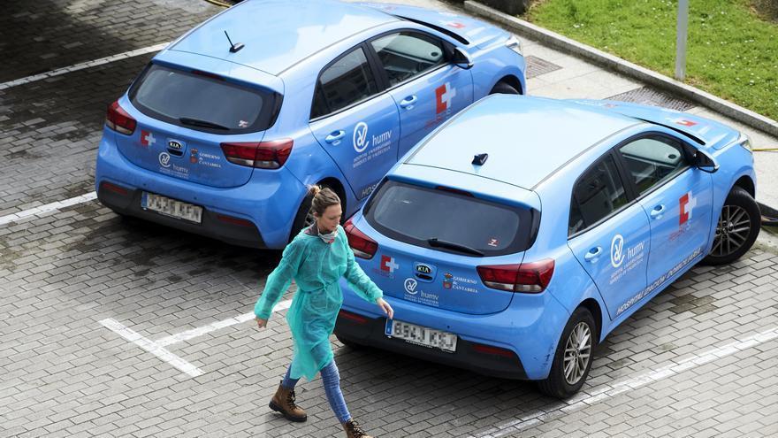 Una profesional sanitaria pasa al lado de vehículos del Hospital  Valdecilla,de Santander. Archivo