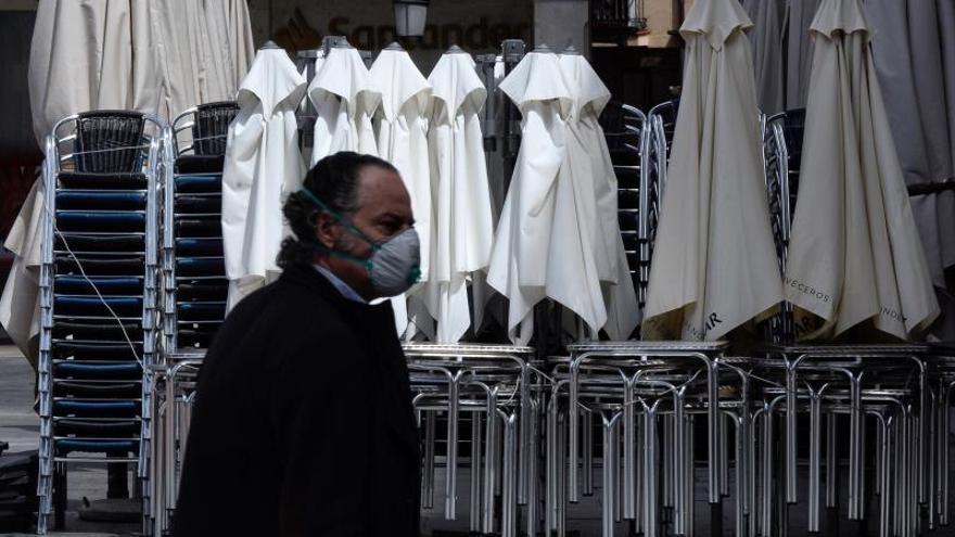 Imagen de archivo de un hombre que pasa frente a una terraza cerrada en estos días de pandemia.